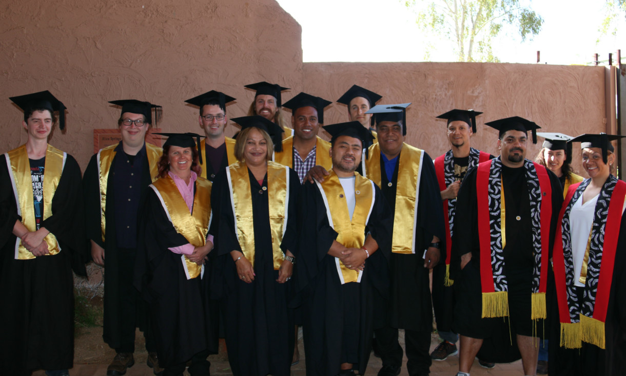 Group of 14 people in graduation robes and caps