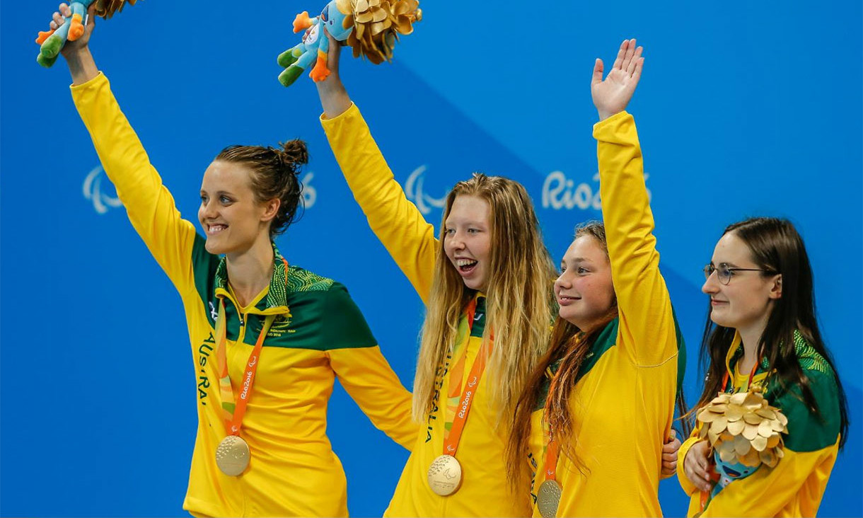 Four happy athletes with their medals, three with their arms up in the air.