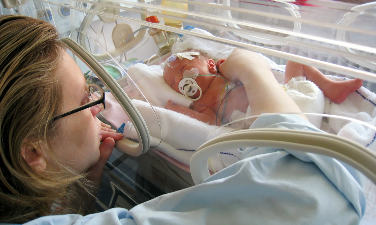 Mother touching her premature baby, who is lying in an incubator