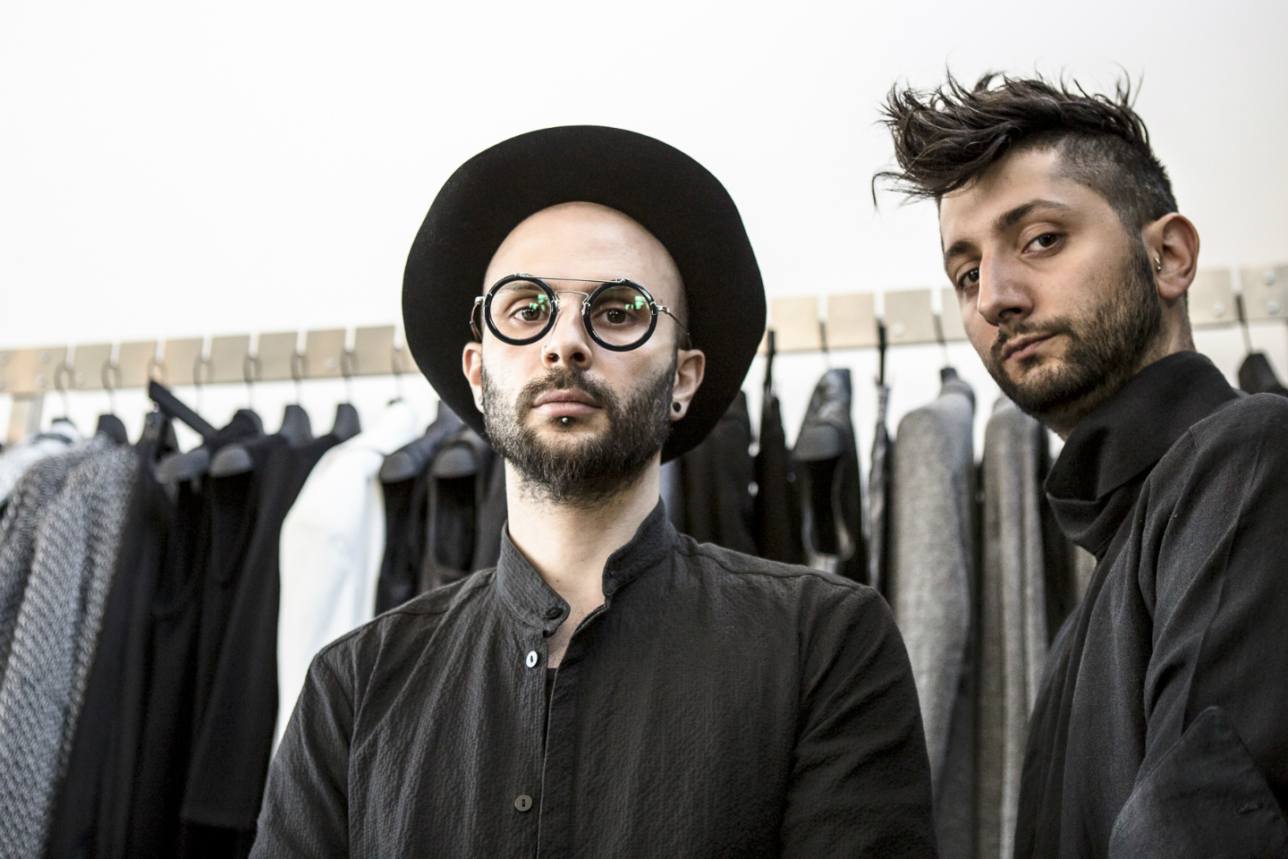 Two fashion designers in front of a rack of clothing