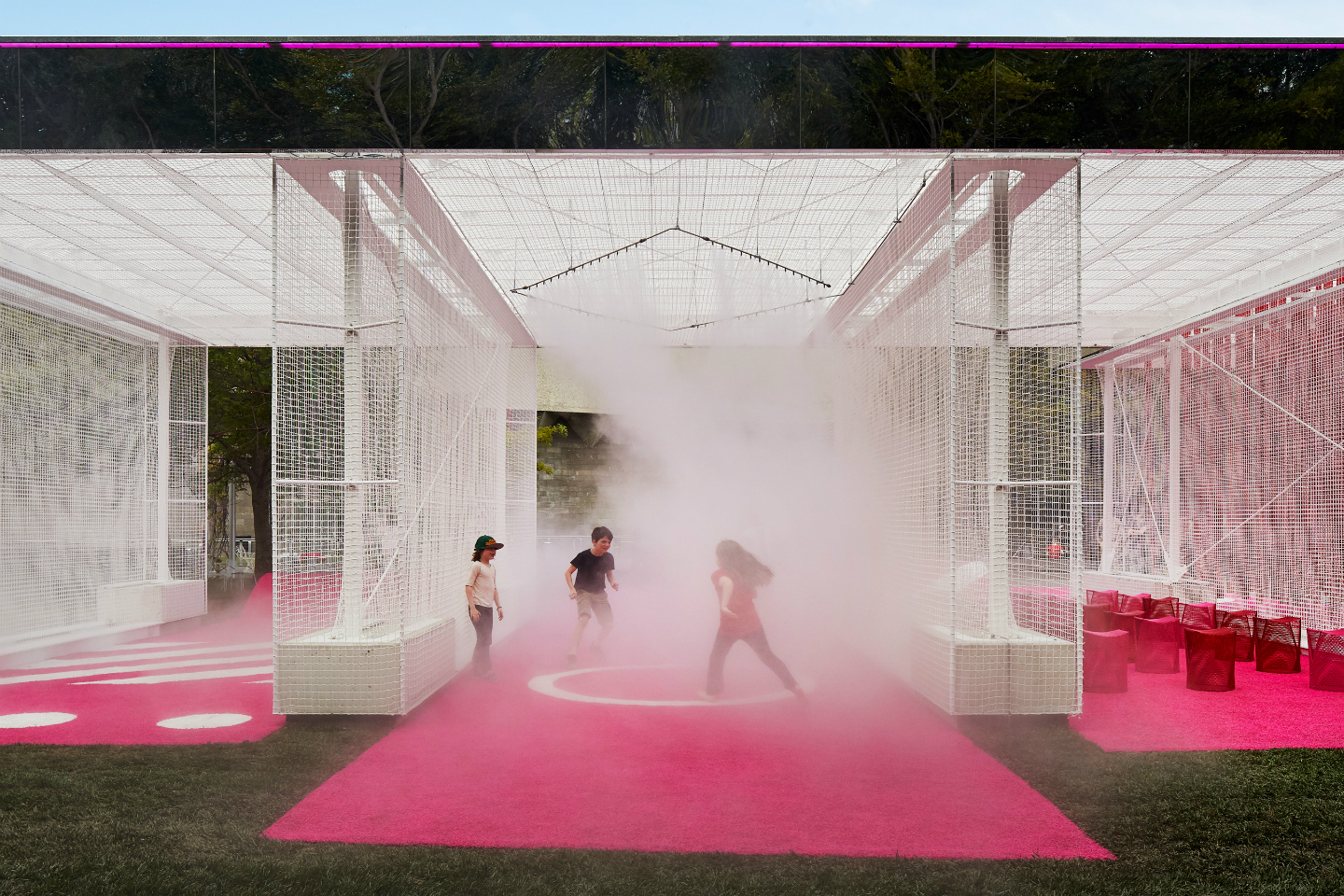 "Children play in a neon pink ""car wash"" at the National Gallery of Victoria"