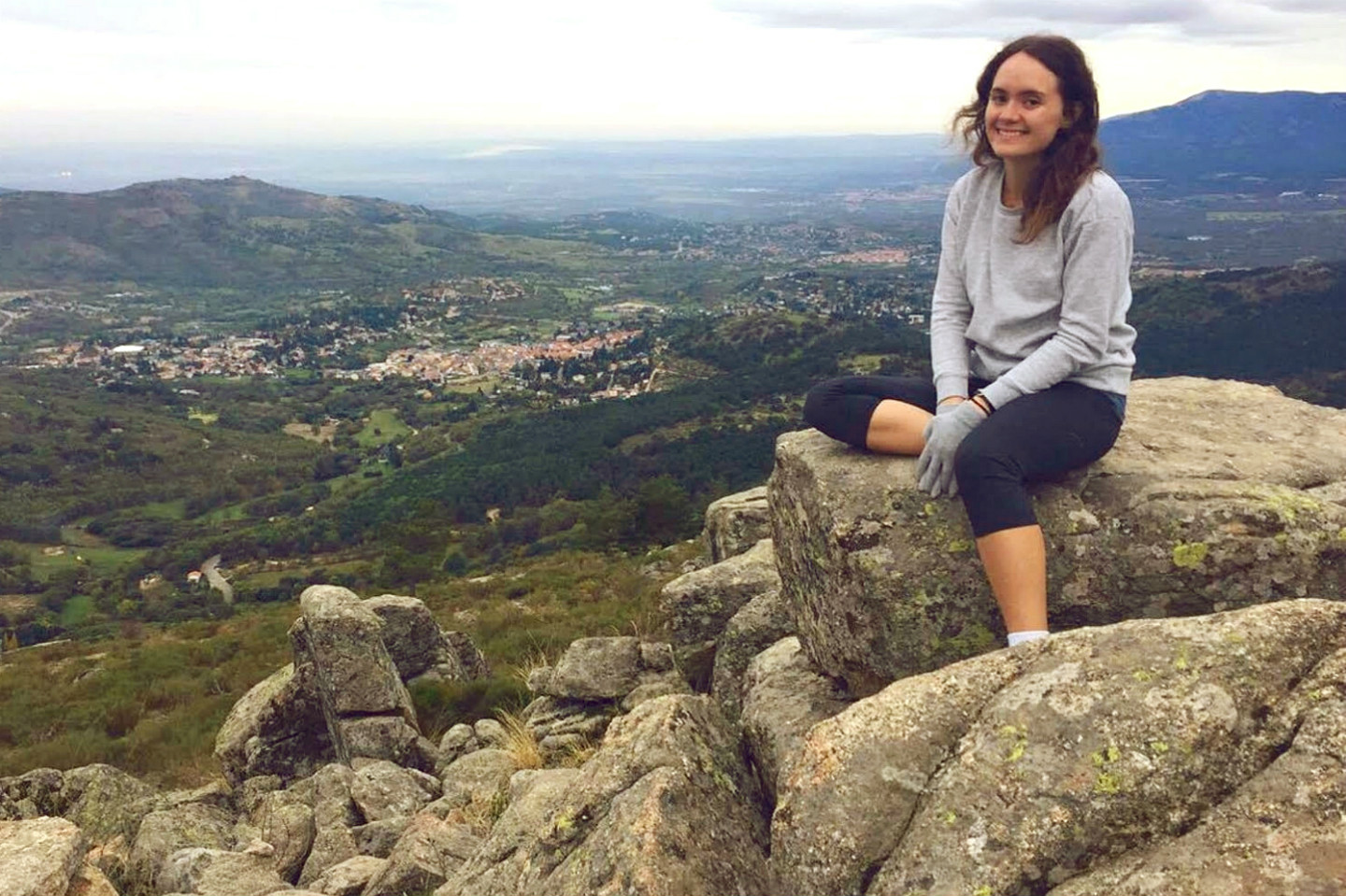 Laura Coburn sitting on a rock, with a view of a plateau behind her