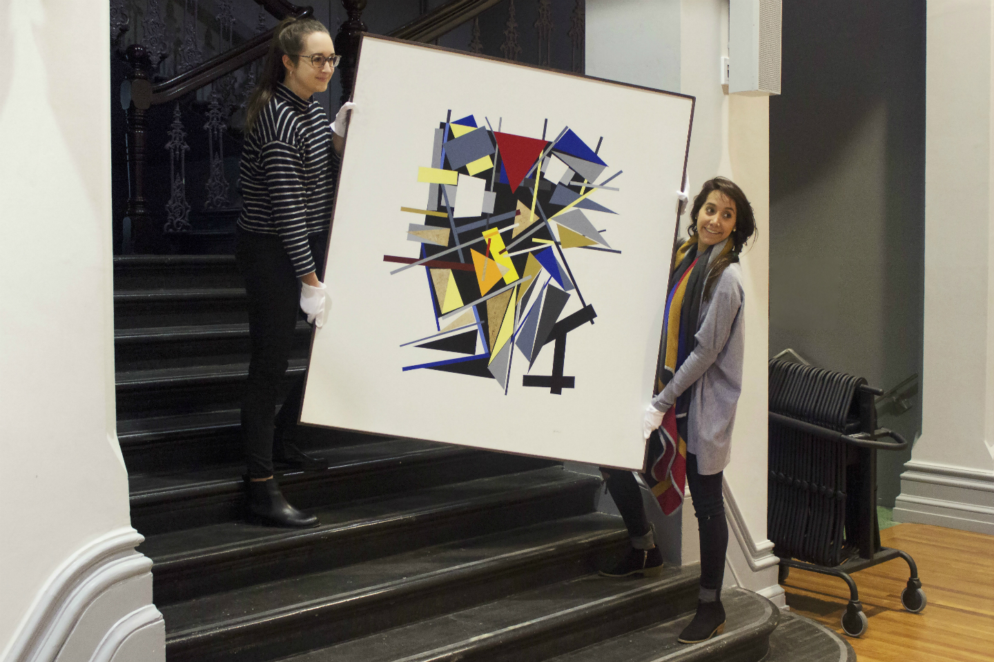 Two students holding a painting at RMIT Gallery