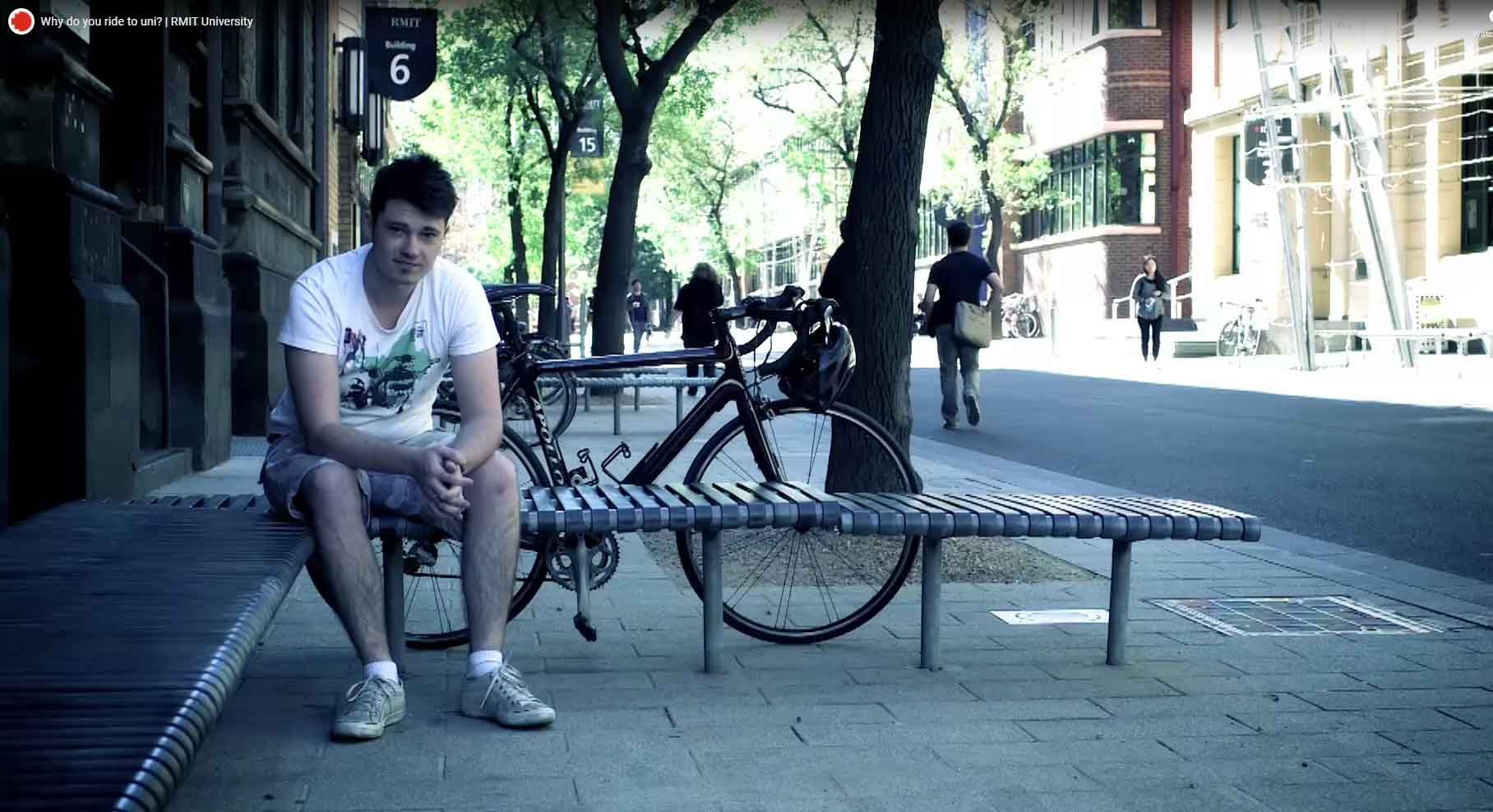 Image of student outside RMIT building with his bike