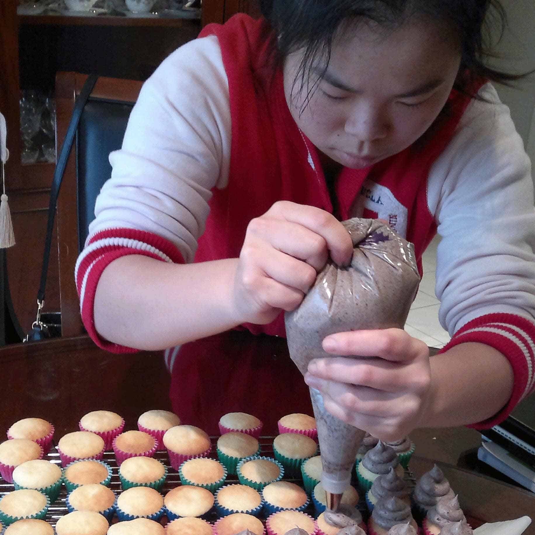Woman piping icing on cupcakes