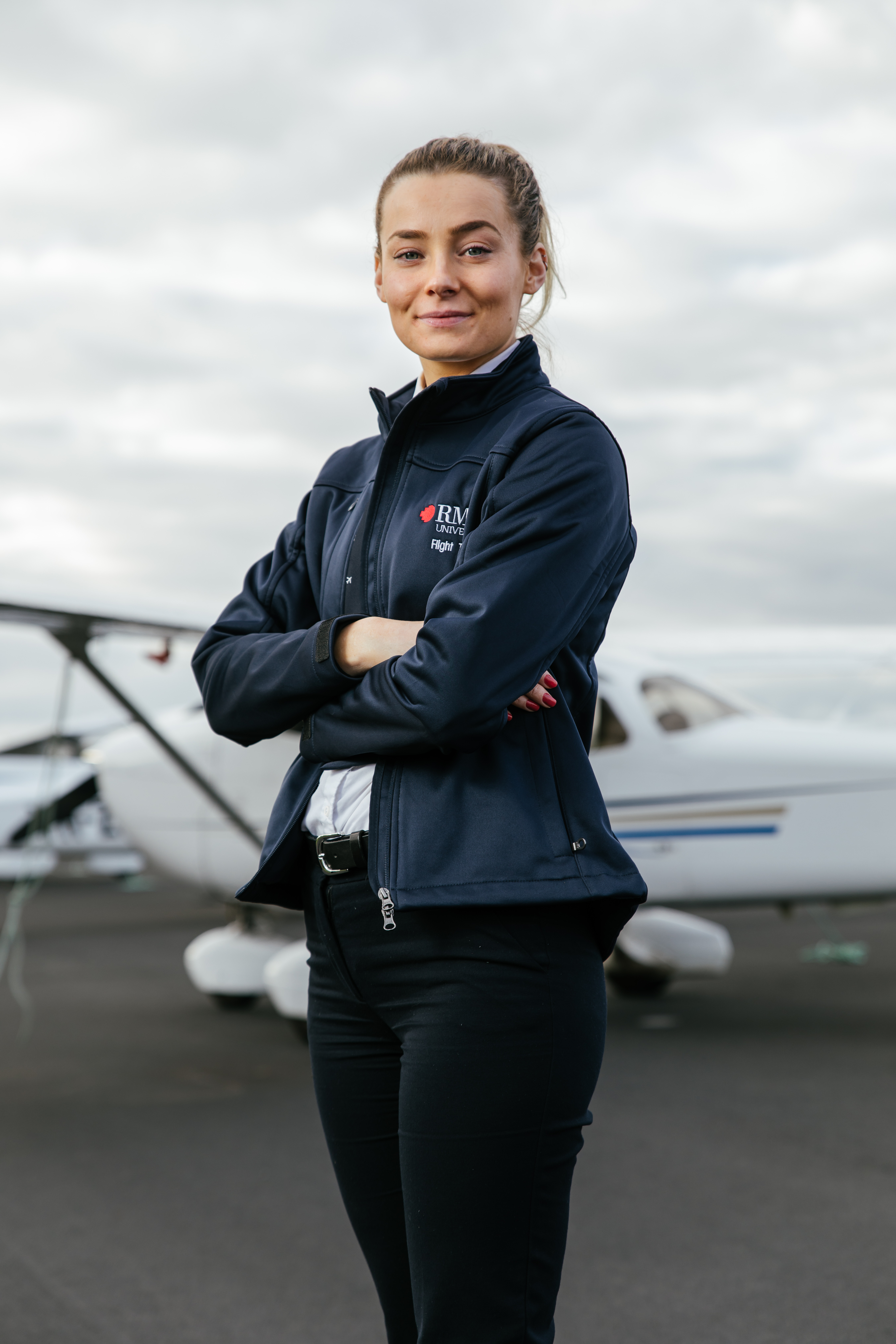Flight training student Kerry Phillips standing in front of a plane