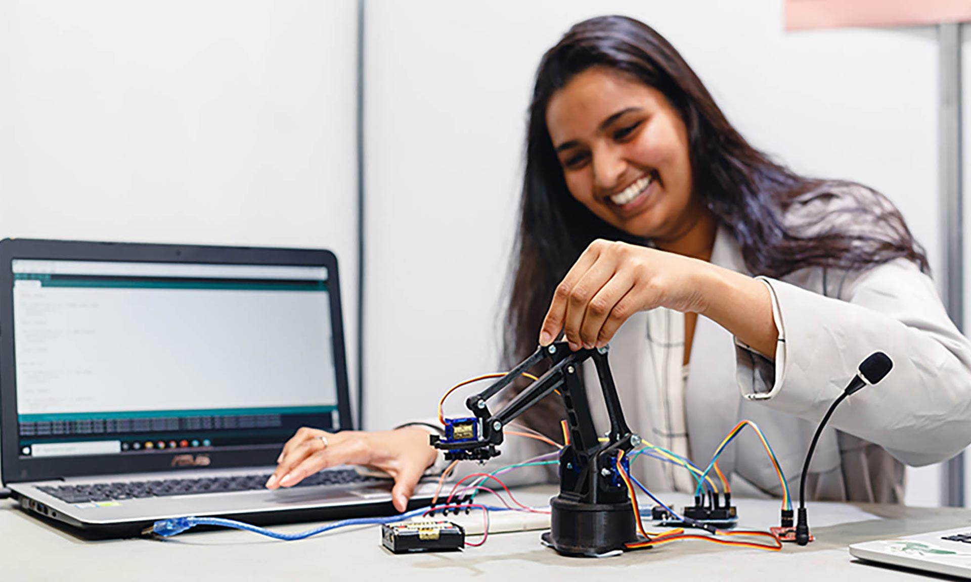 female student smiling and using robot arm kit with laptop open