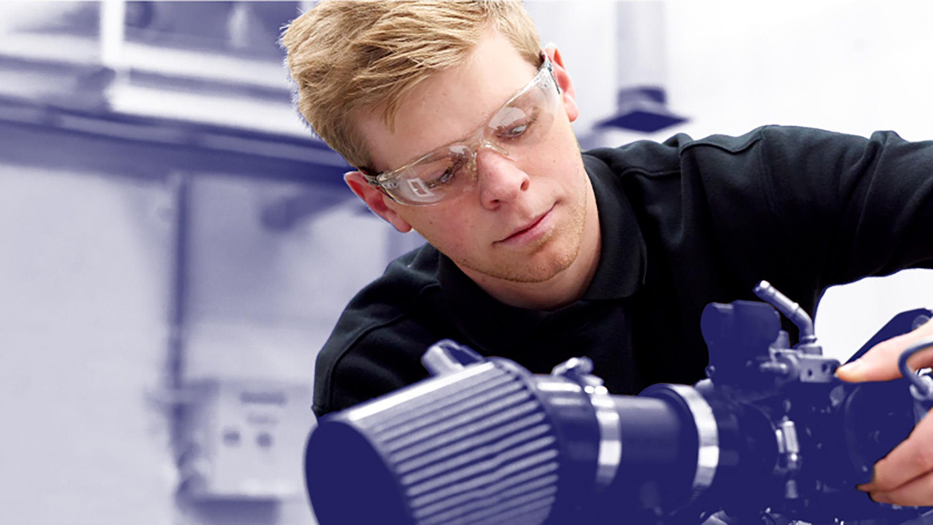 male student using science equipment wearing safely glasses