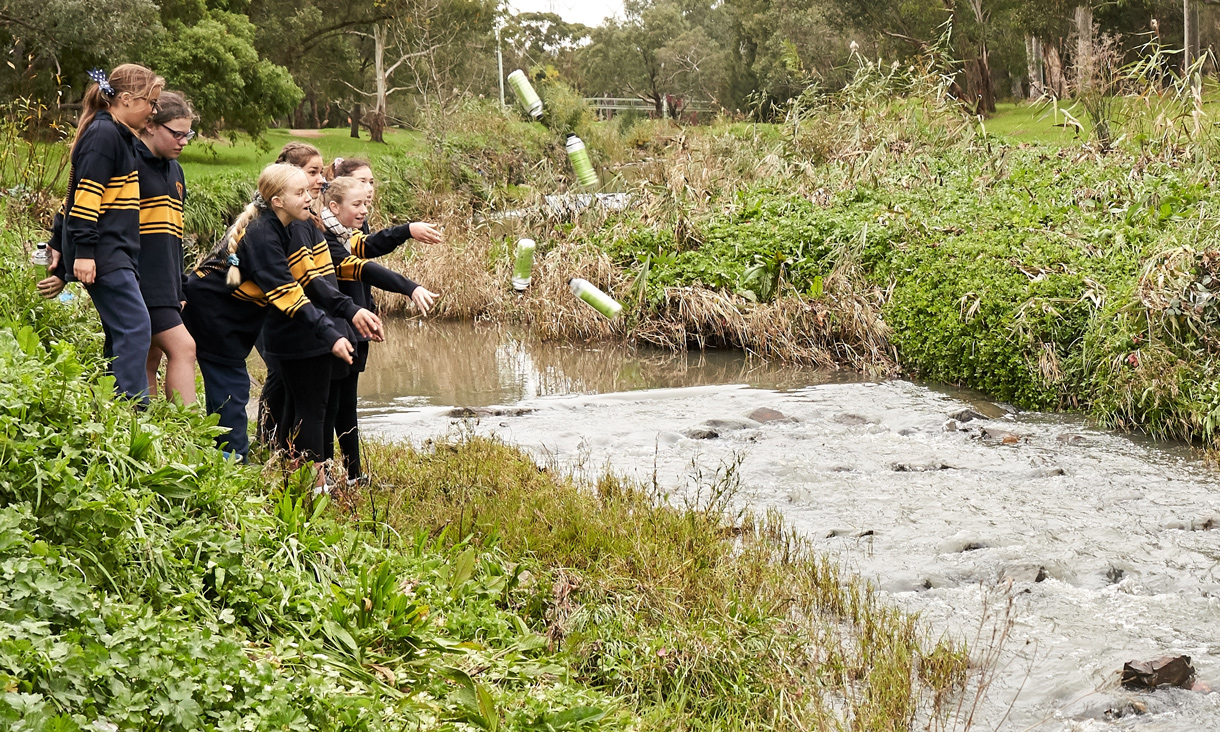 Children throwing litter trackers into a creek