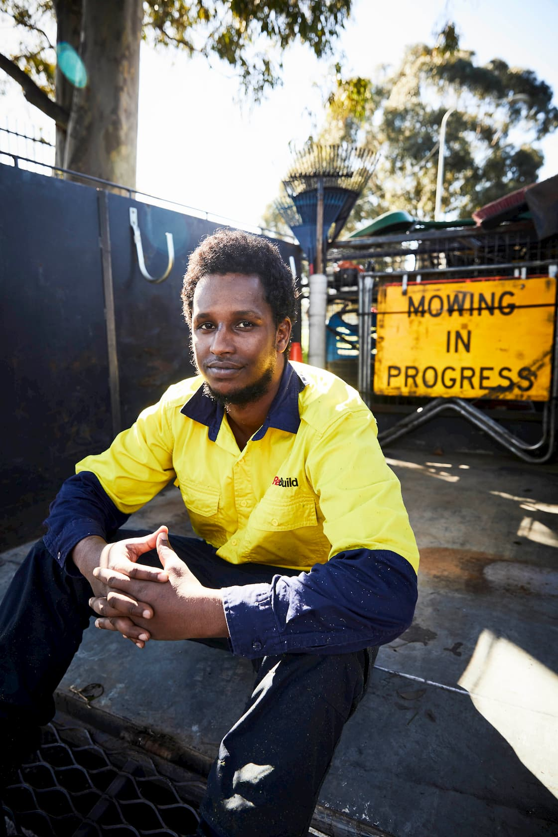 A man sitting alongside fencing and signs in work clothing.
