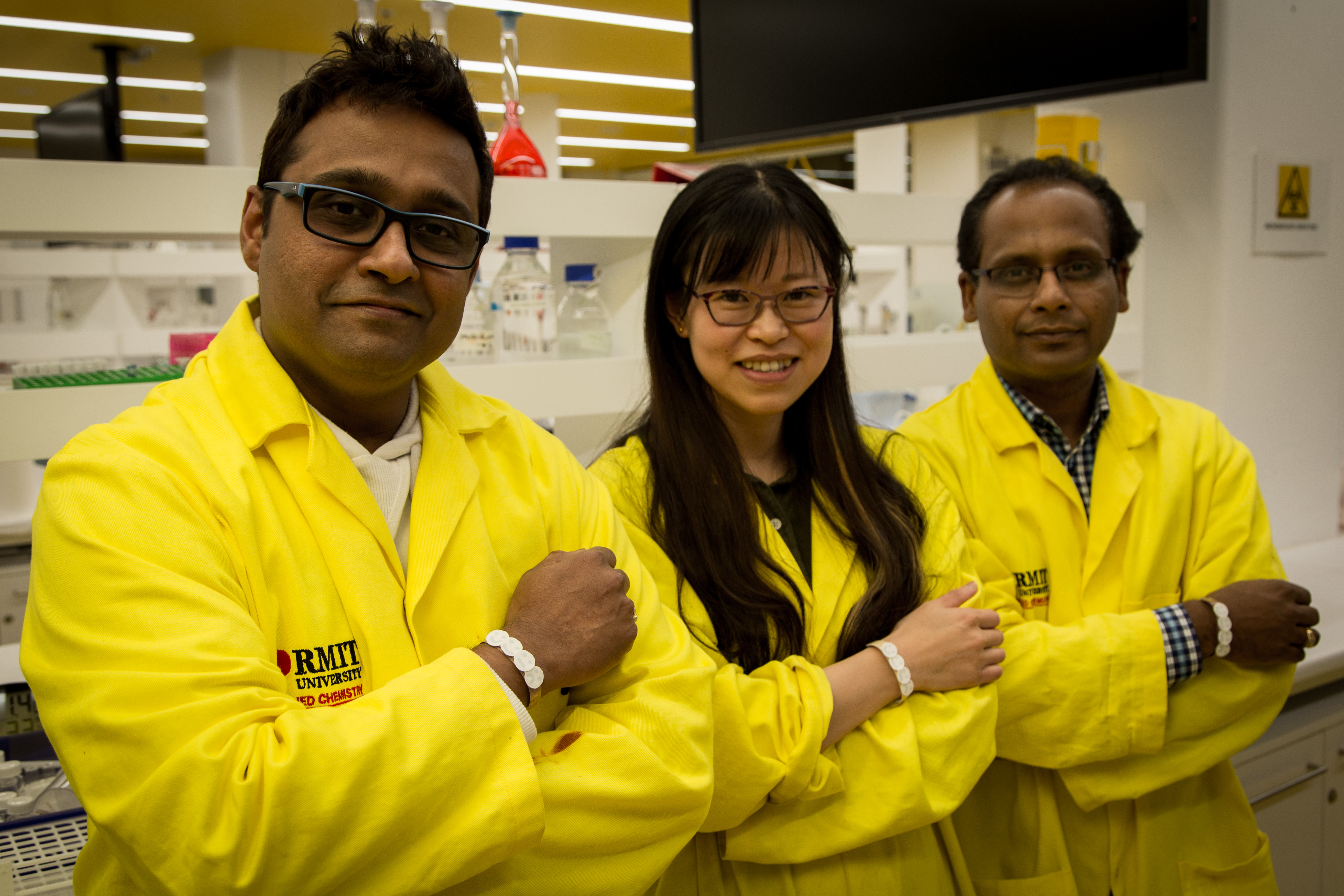 RMIT researchers from the Ian Potter NanoBioSensing Facility wearing prototypes of their UV sensor, from left to right, Dr Rajesh Ramanthan, PhD candidate Wenyue Zou and Professor Vipul Bansal.