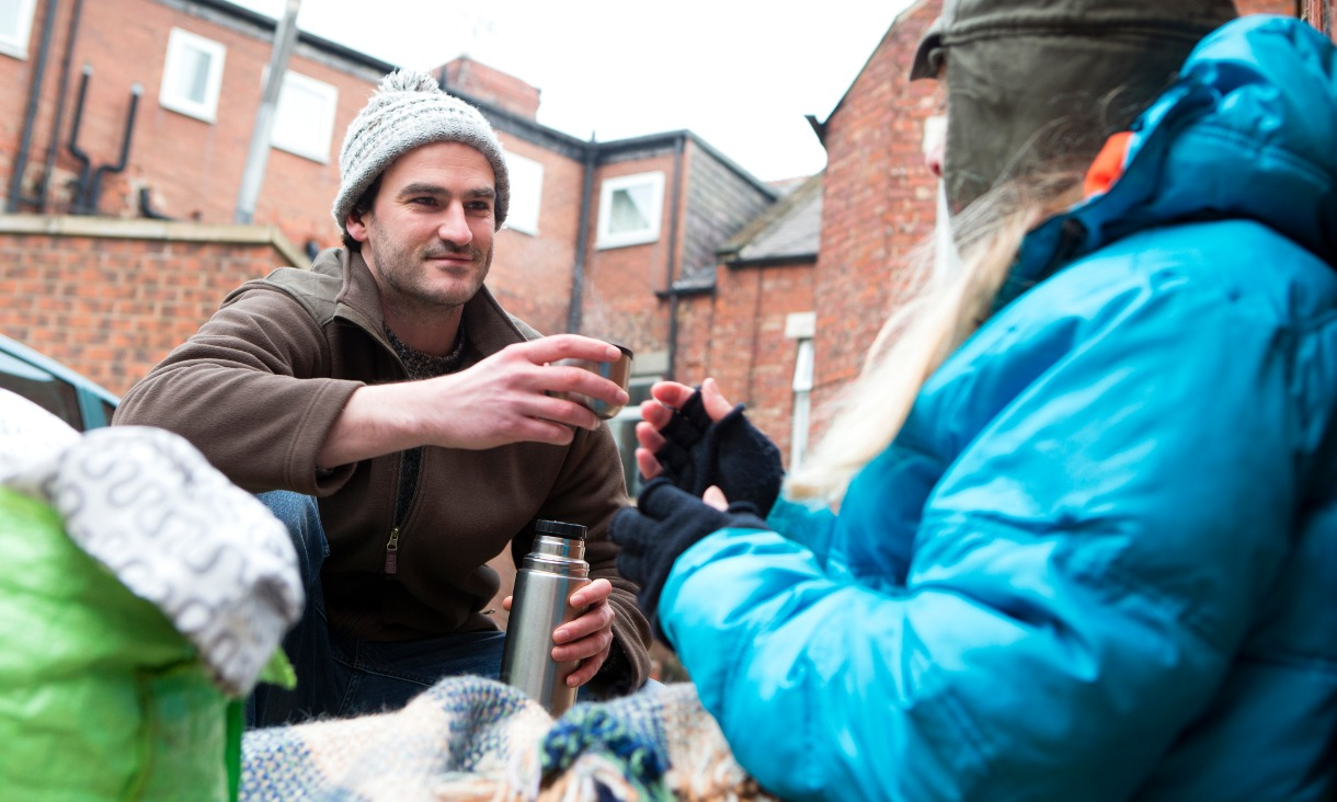 Man giving homeless a hot drink for charity.