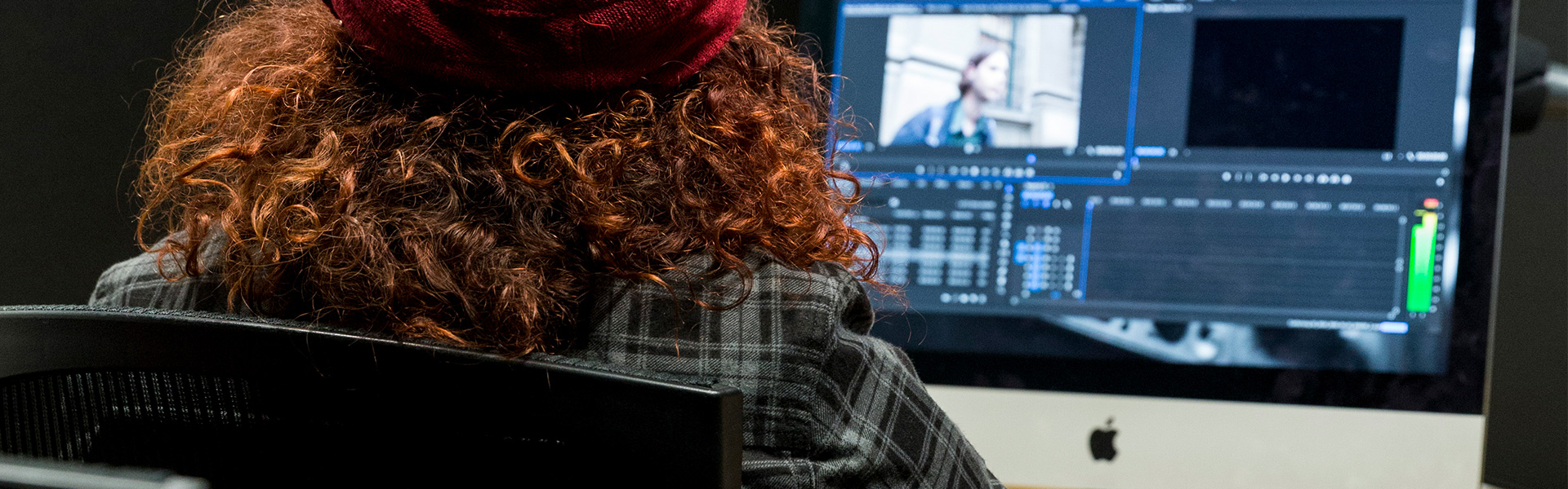 Woman sitting at computer editing video