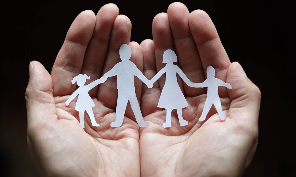 Hands hold white paper cutout of two children and two adults