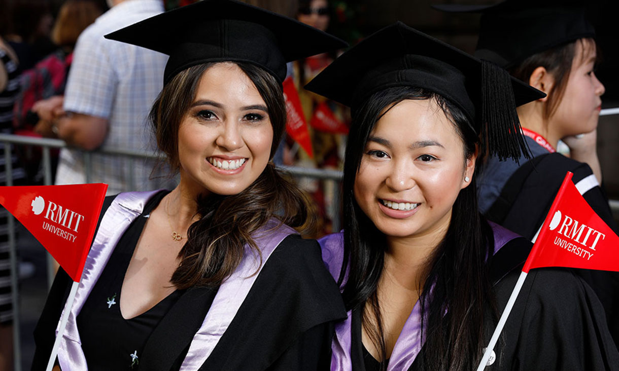 Two RMIT students smiling and waving RMIT flags
