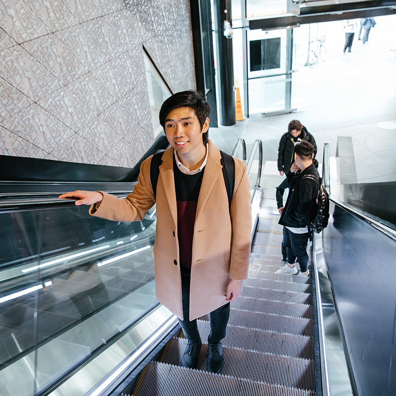 Young man standing on escalator