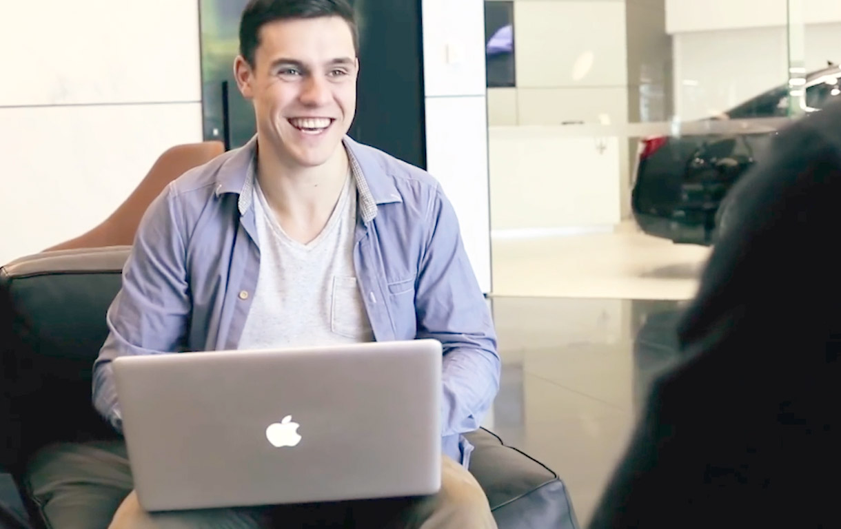 Business student smiling with open laptop