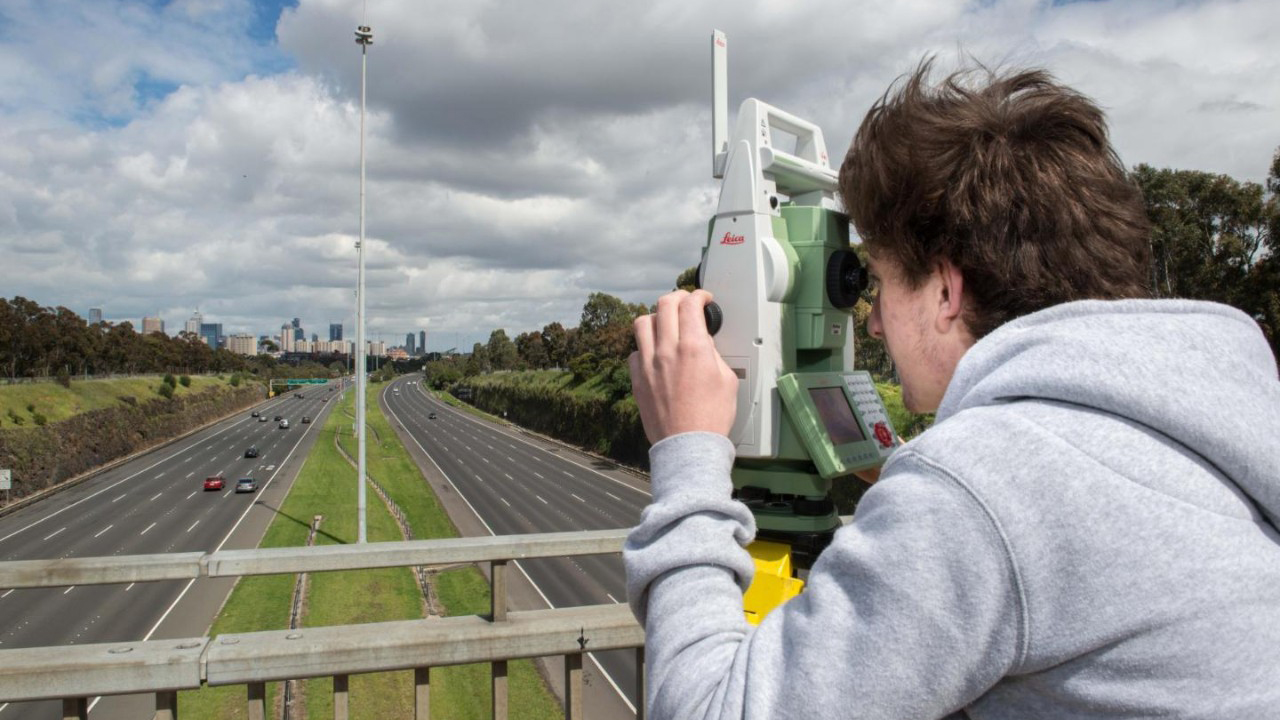 Student using a theodolite on a motorway