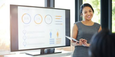 Woman presenting data on whiteboard