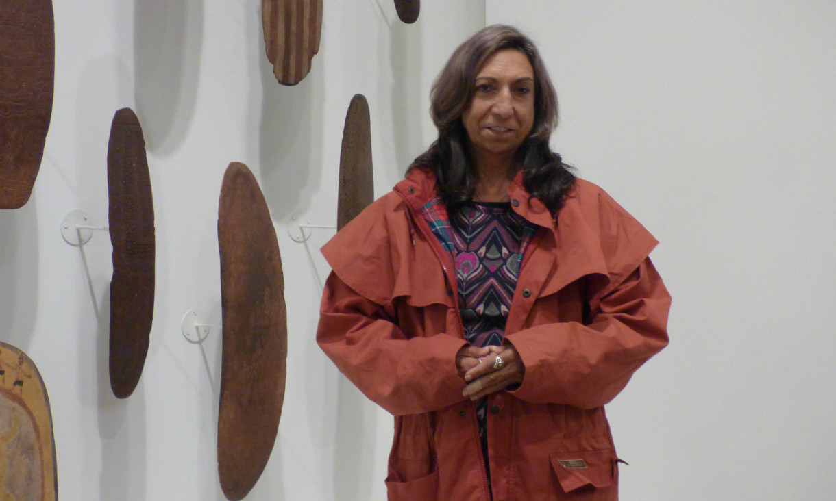 Artist stands in front of wall of Indigenous shields.