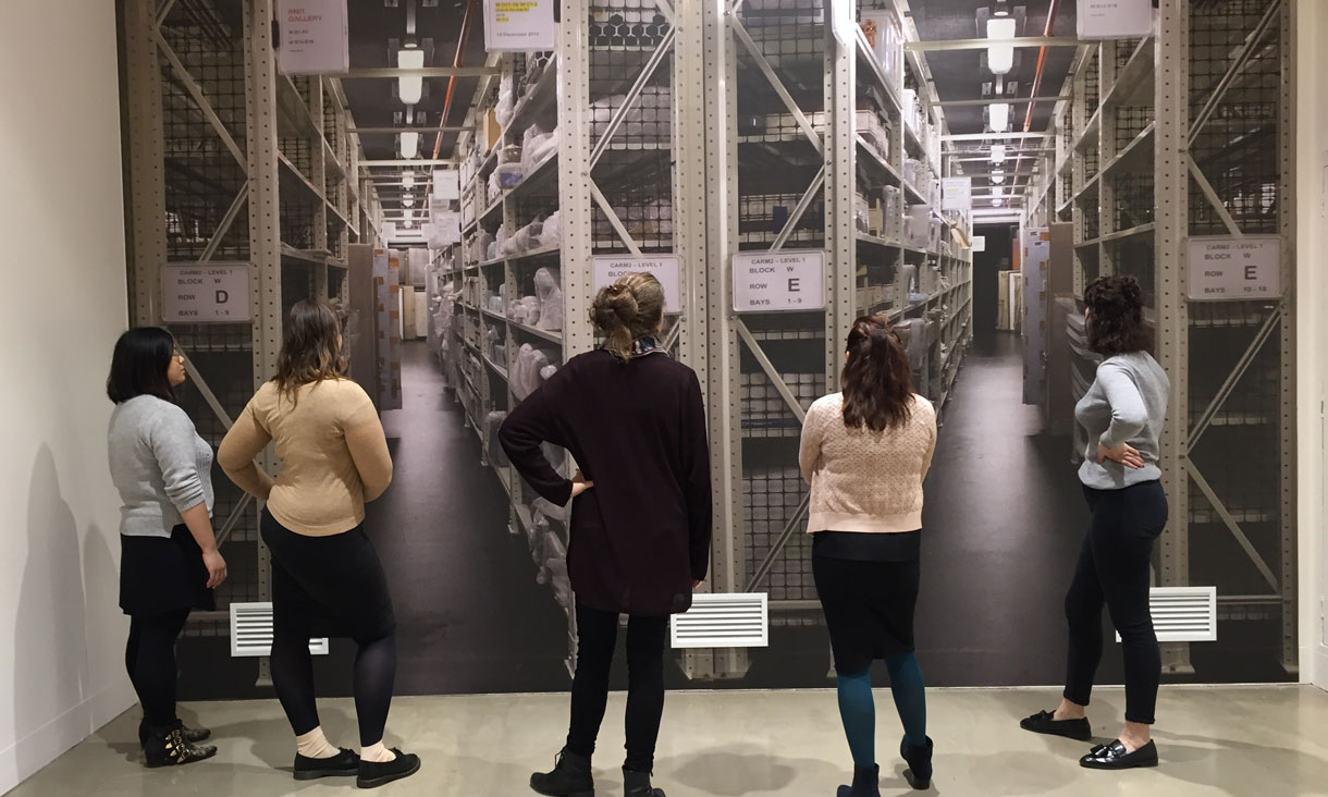 Master of Arts (Arts Management) students stand in a line looking into the gallery storage cages lined with archived artworks.