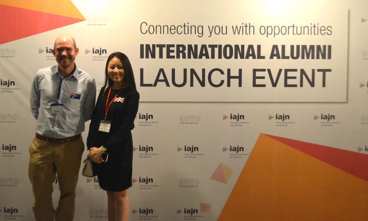 "Two people standing in front of a sign saying ""international alumni launch event"""