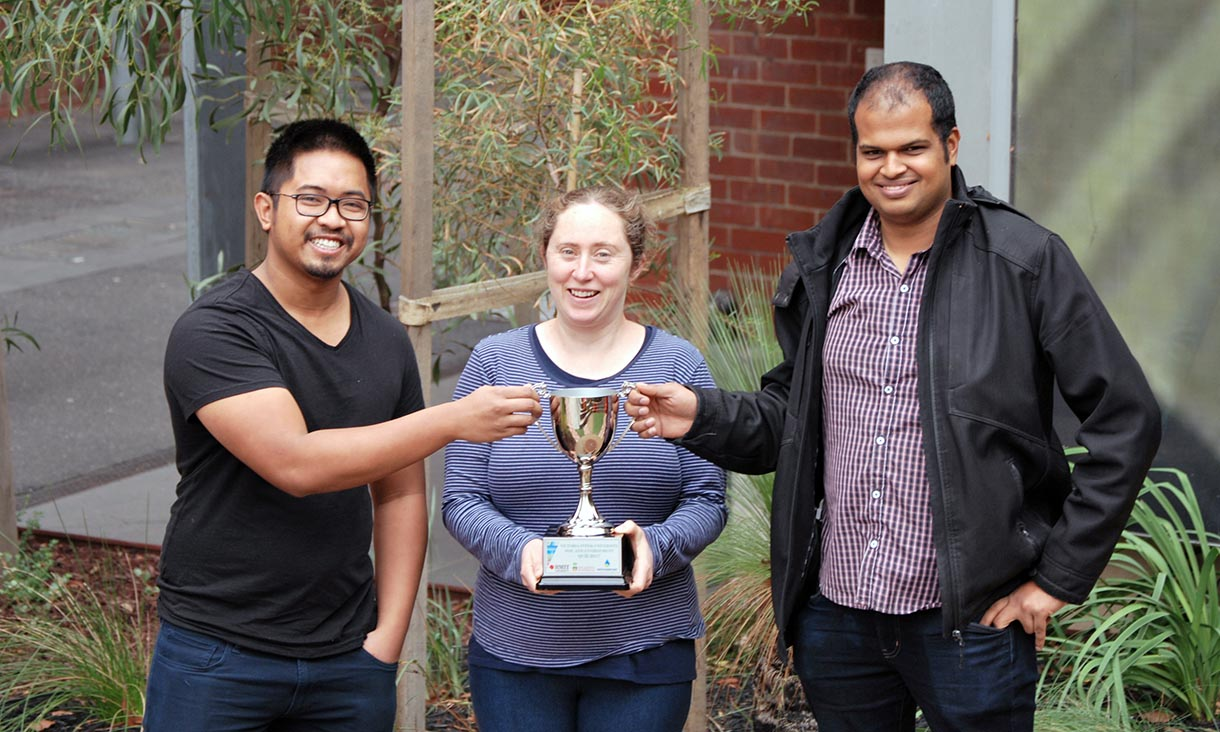 Left to right: RMIT students Dexter Villanueva, Christine Close and Nihal Albuquerque display their hard won trophy.