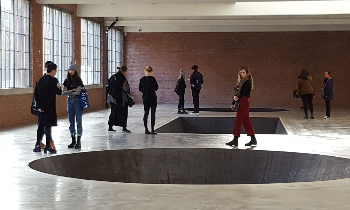 Huge geometric holes cut into the floor of a gallery space