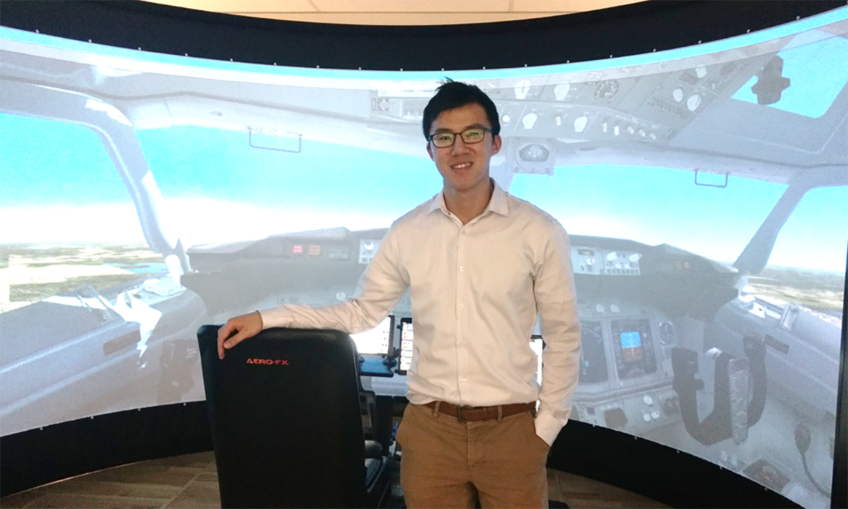 Student standing in front of simulator and screen.