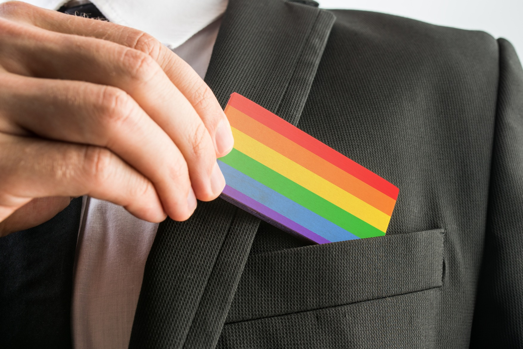 Person putting rainbow card in business suit jacket pocket