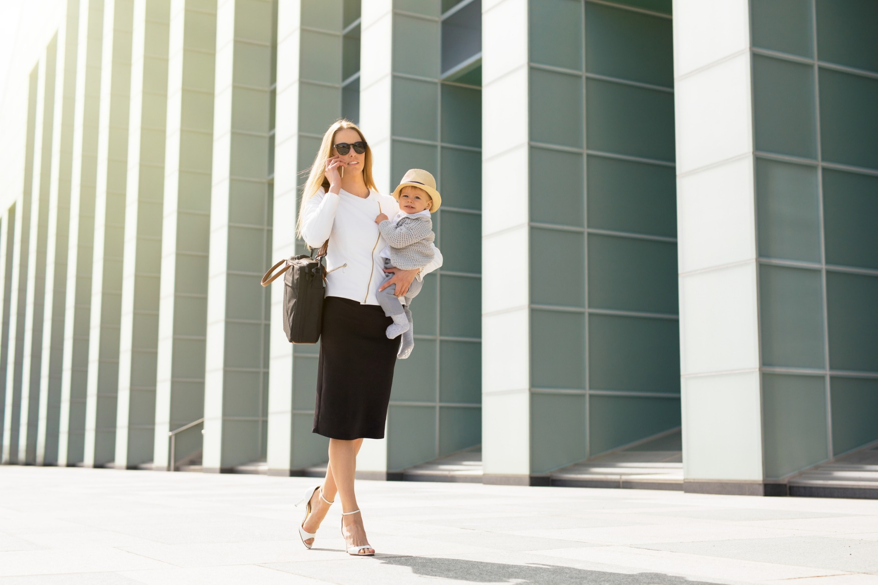Mother in business clothes, carrying baby.