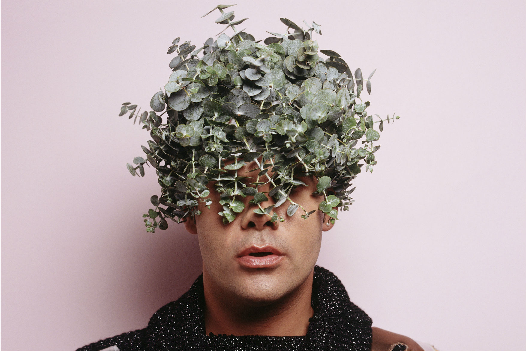 Man with plants half covering face