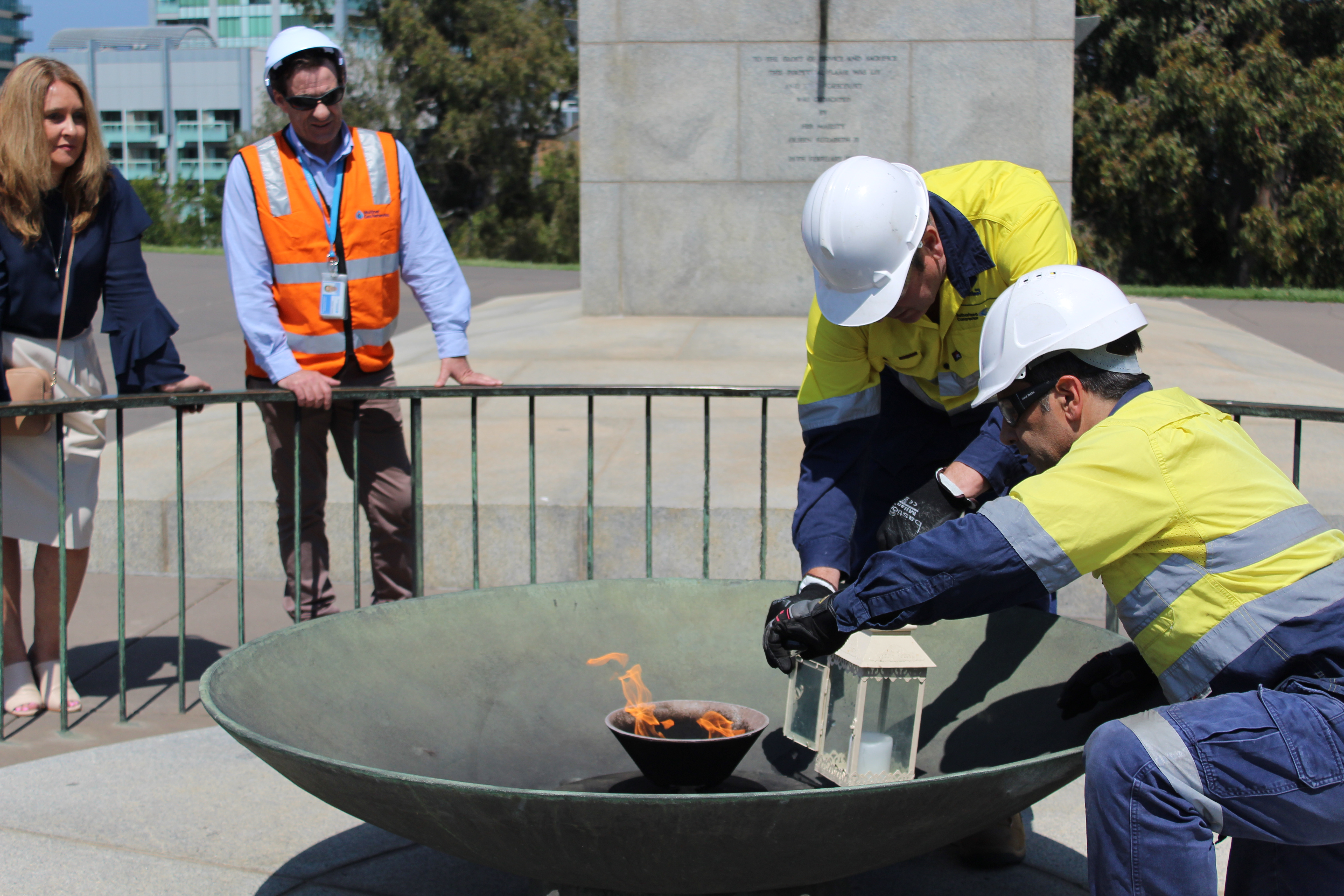Workers keep the flame alive inside a lantern during installation of the new burner.