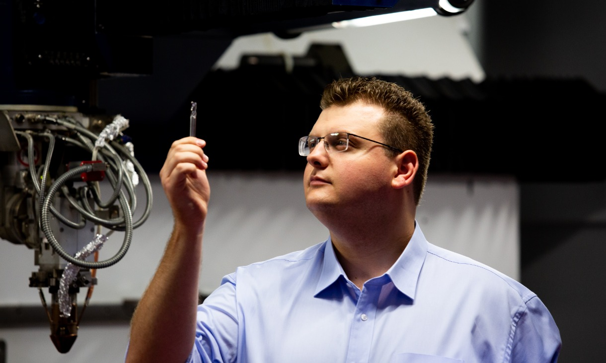 PhD student Jimmy Toton inspects a 3D-printed steel tool.