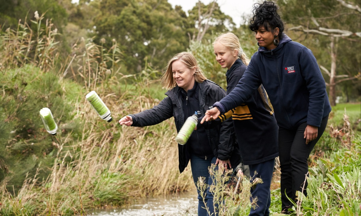 Melbourne Water's Litter and Waterwatch Coordinator Naomi Dart, citizen scientist and Bentleigh West Primary School student Sophie Littlefair and RMIT's Dr Kavitha Chinathamby launching GPS-tracked bottles into Dandenong Creek.