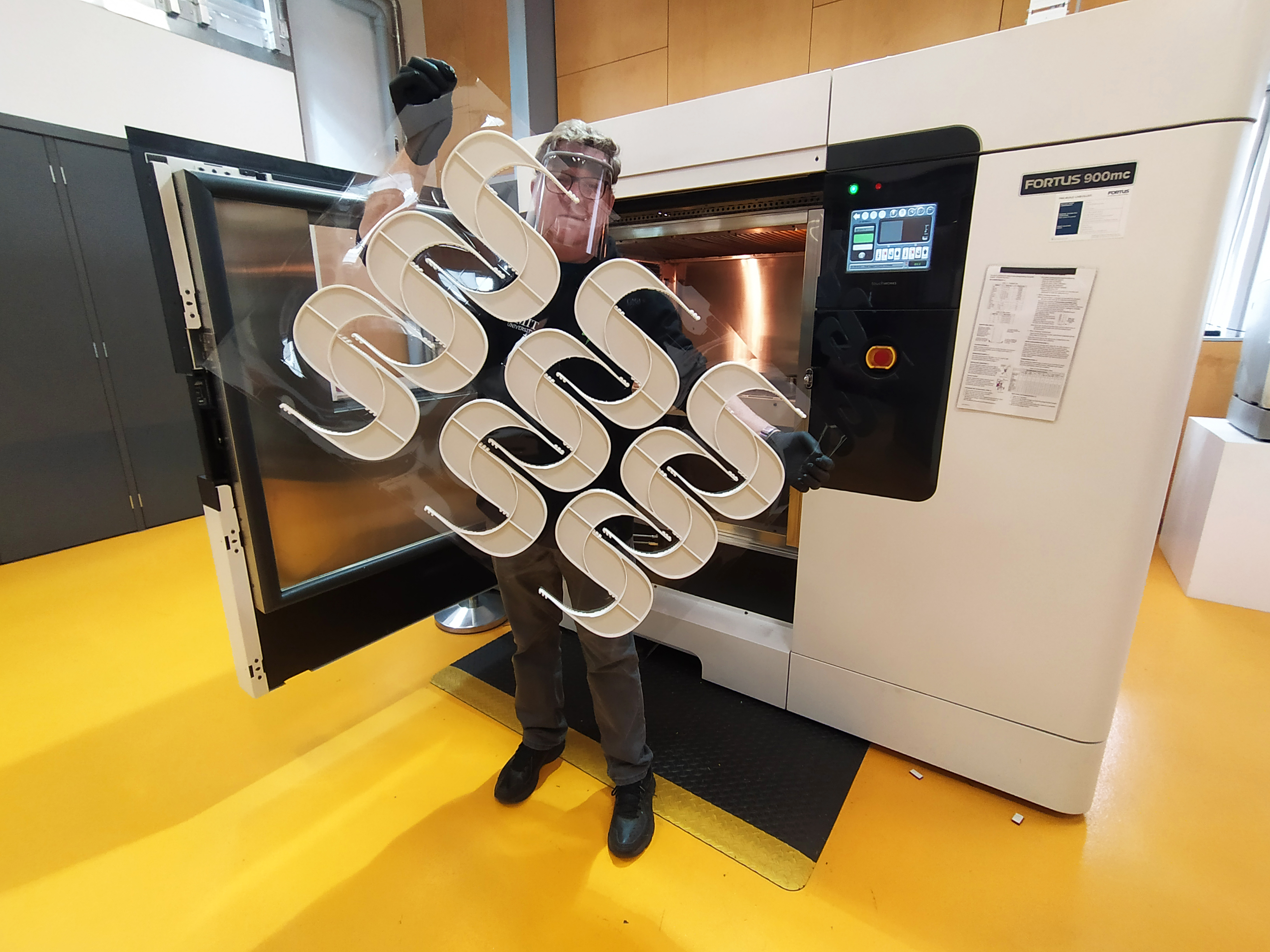 RMIT's Paul Spithill with a batch of the 3D printed plastic face shield frames.