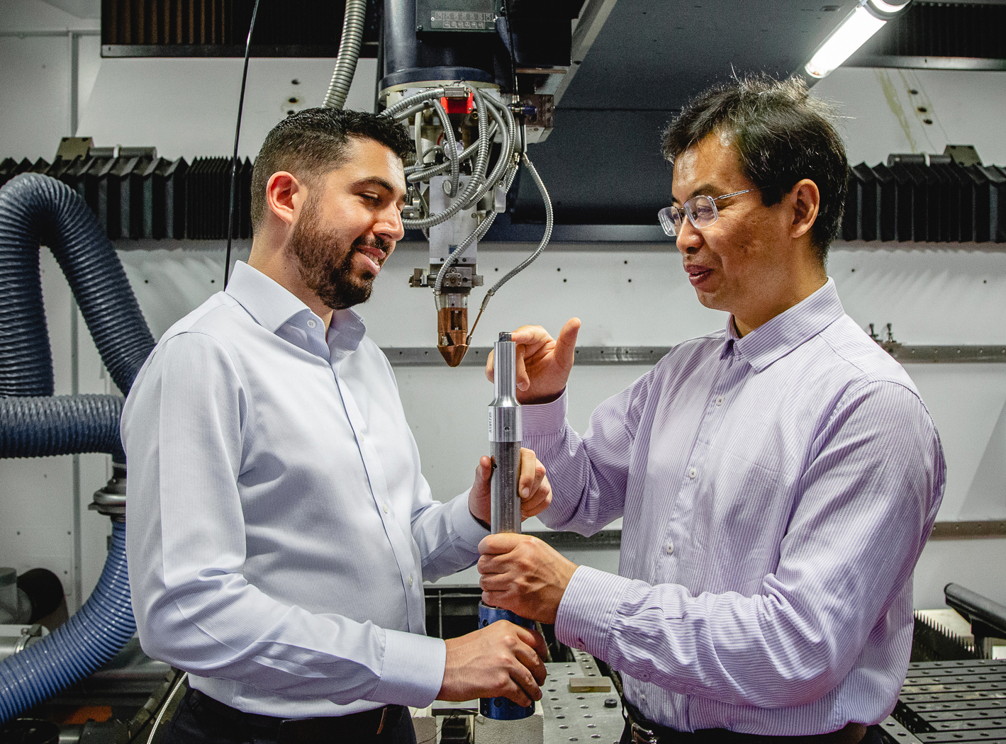Carmelo Todaro and Ma Qian inspect a 3D printed Titanium alloy cube on the tip of an ultrasound rod.