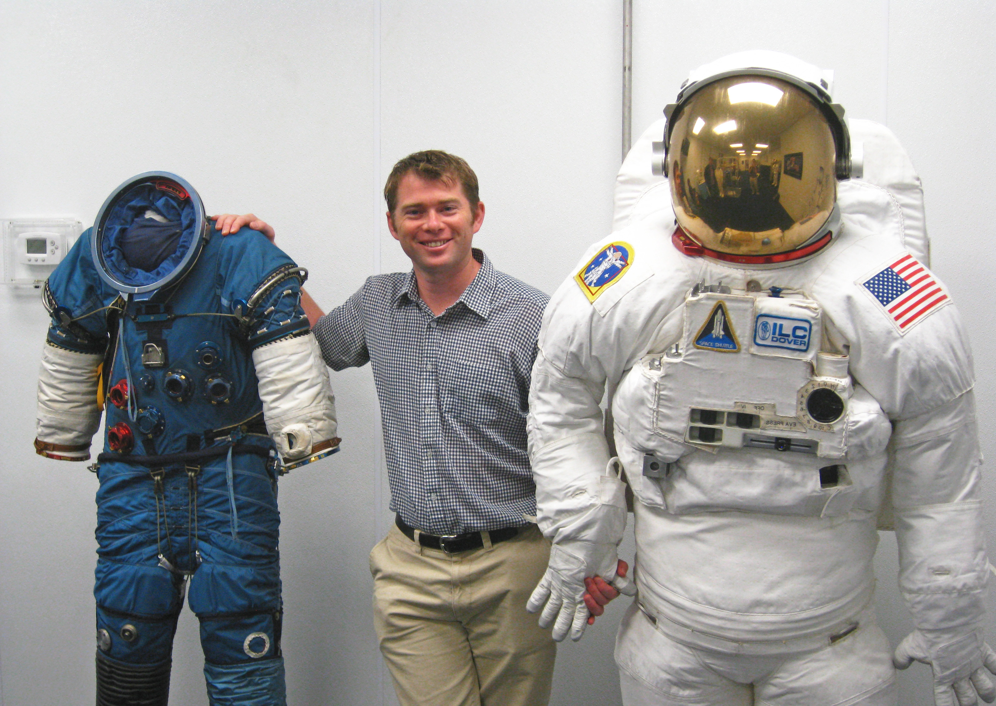 RMIT alumnus and Chief Engineer at Human Aerospace, Dr James Waldie, poses with NASA Extravehicular Activity suits used for spacewalking.