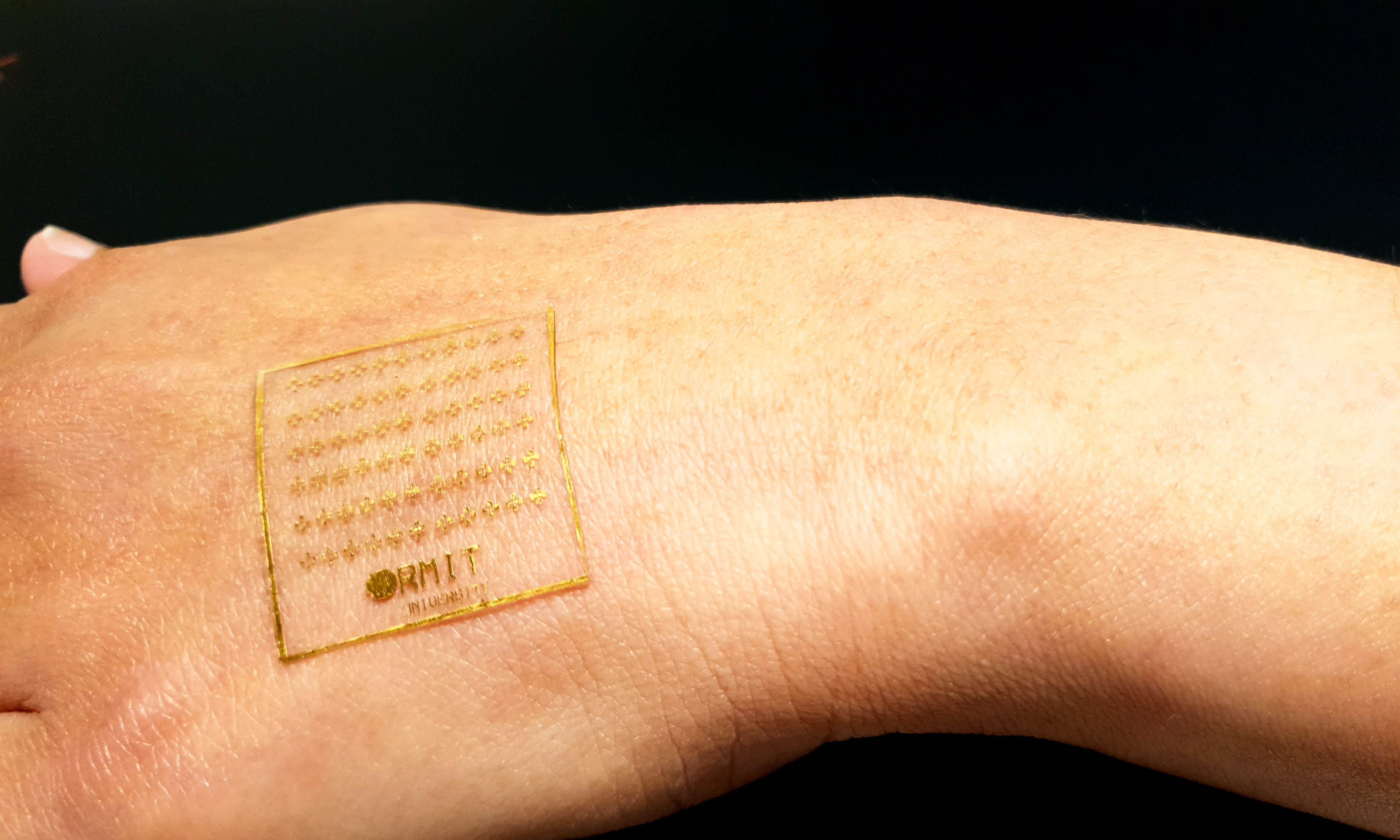 Clear stretchable electronic device on the back of a hand.