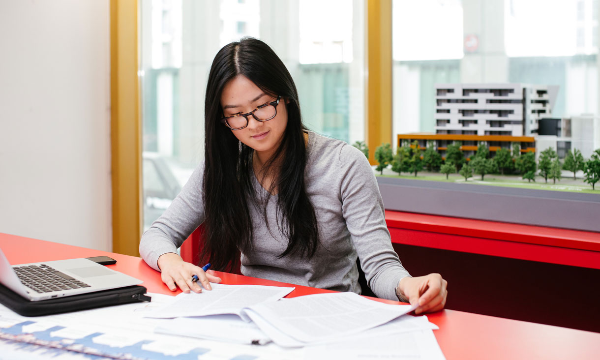Student Catherine Lai examines property development documents at her desk. In the background is a model of a city.