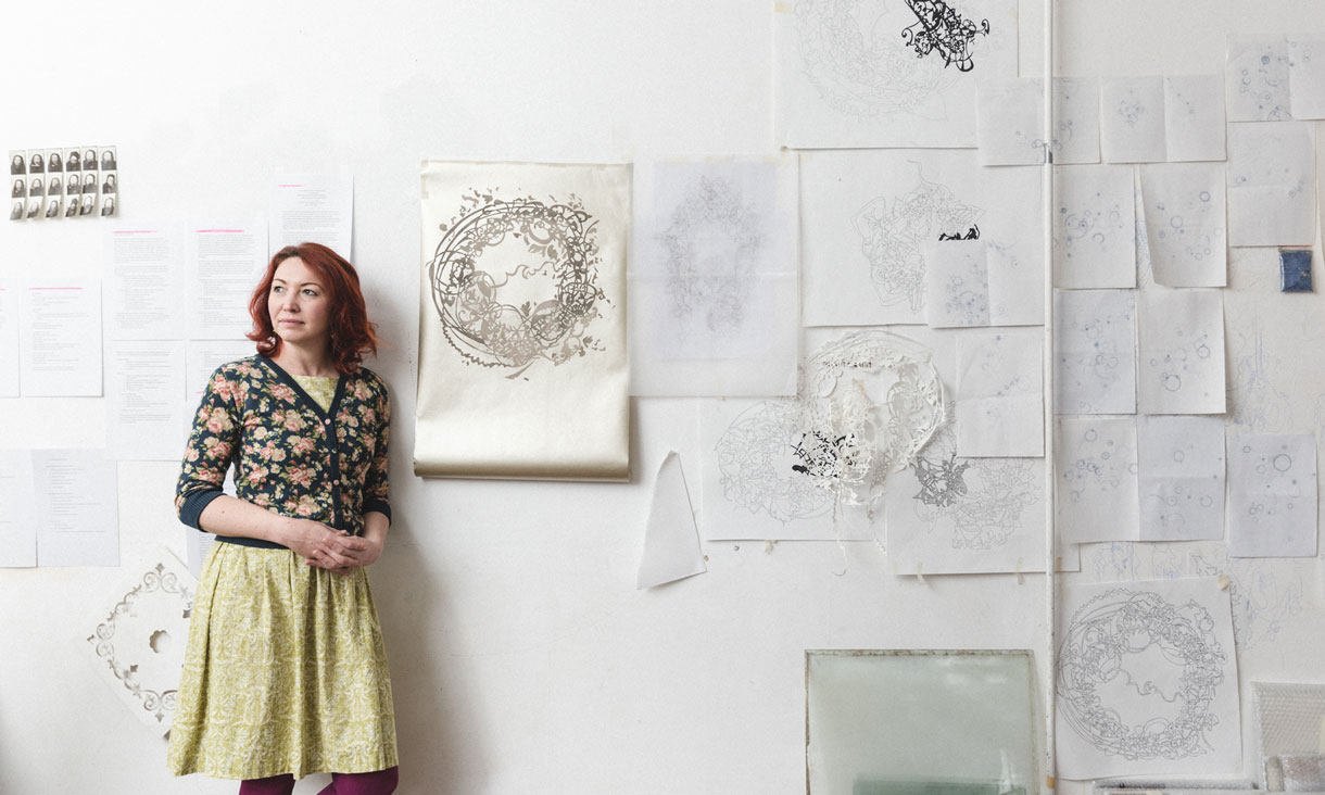 Hannah stands in her studio leaning on a wall covered in drawings and paper templates.