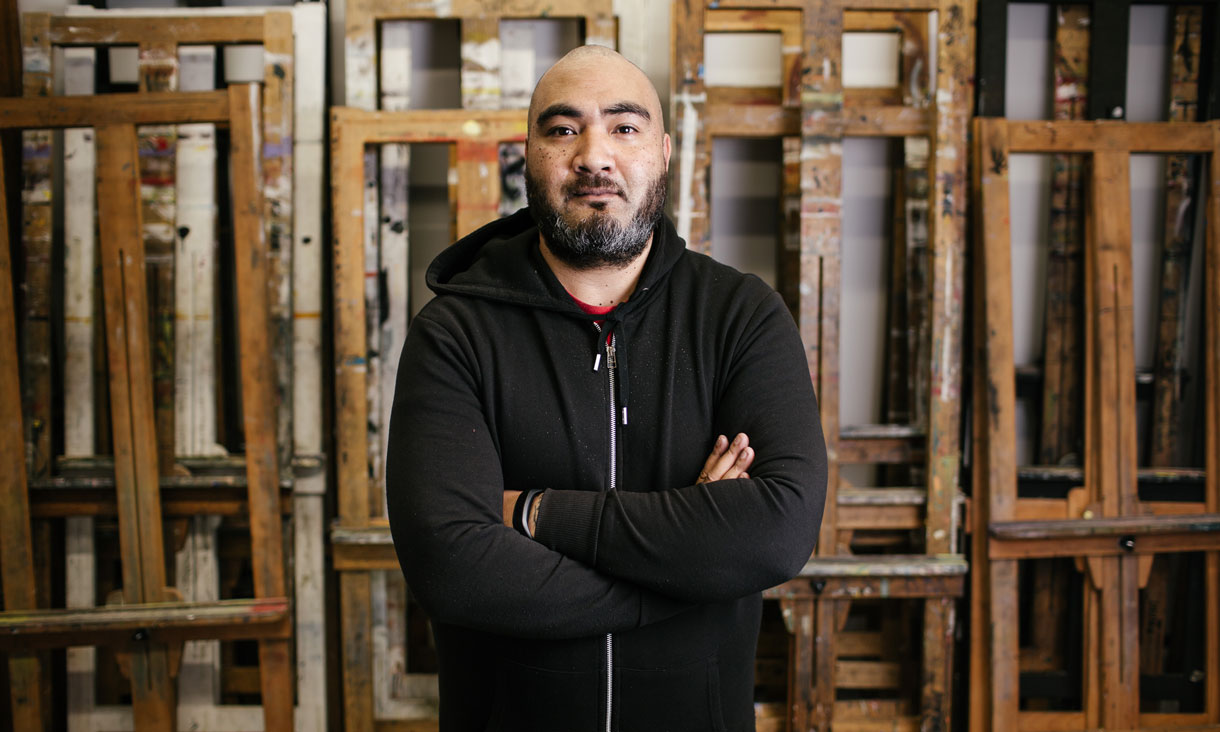 Portrait of Ite Mauga with arms crossed standing in front of art easels.