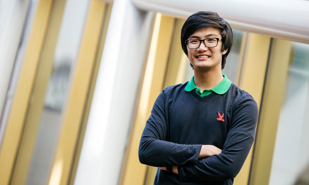 Student Jamie Ung stands smiling with arms crossed in front of an RMIT building.