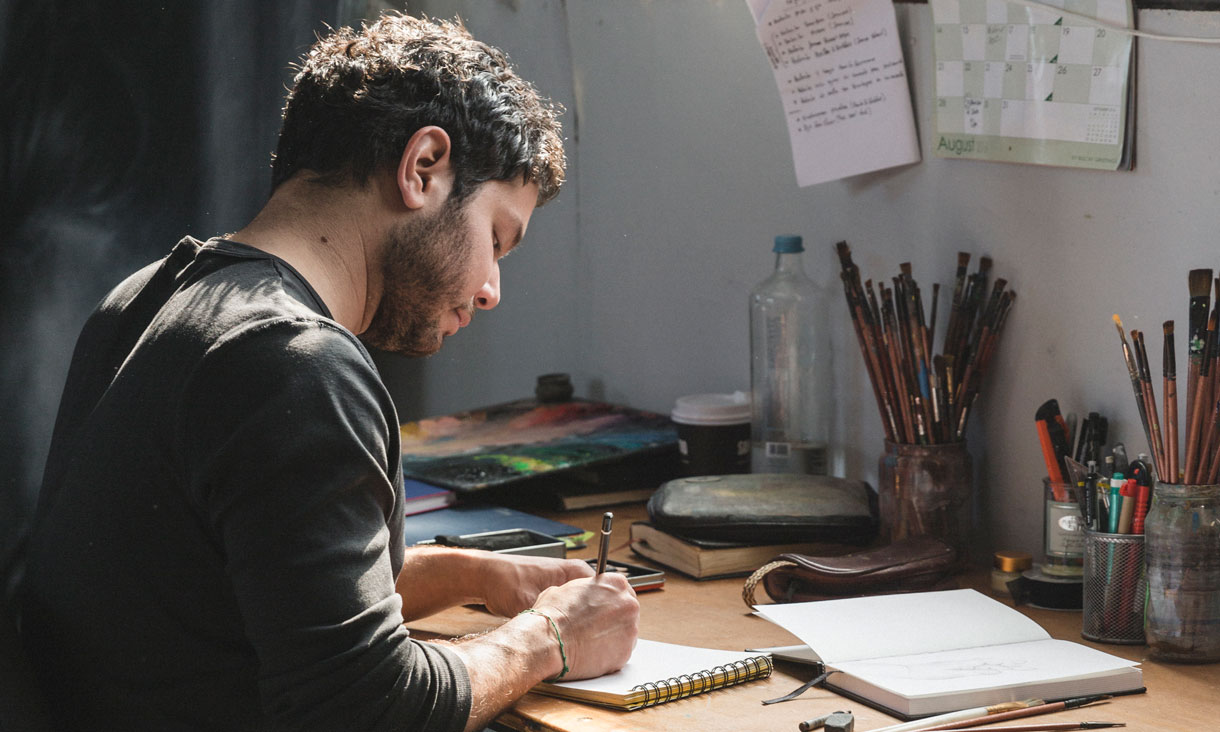 Julian Clavijo sits at his studio desk working in his sketchbook.