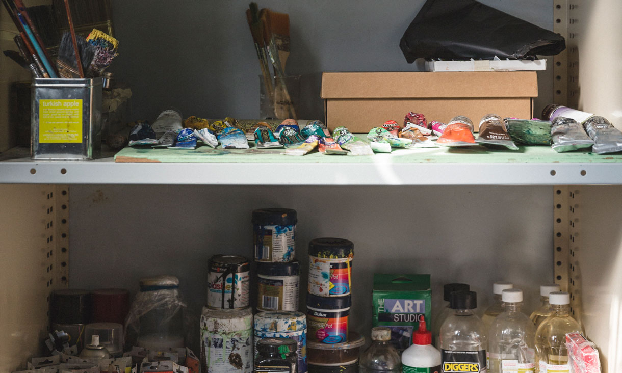 Tubs and tubes of paint and other materials on a shelf in the artists studio.