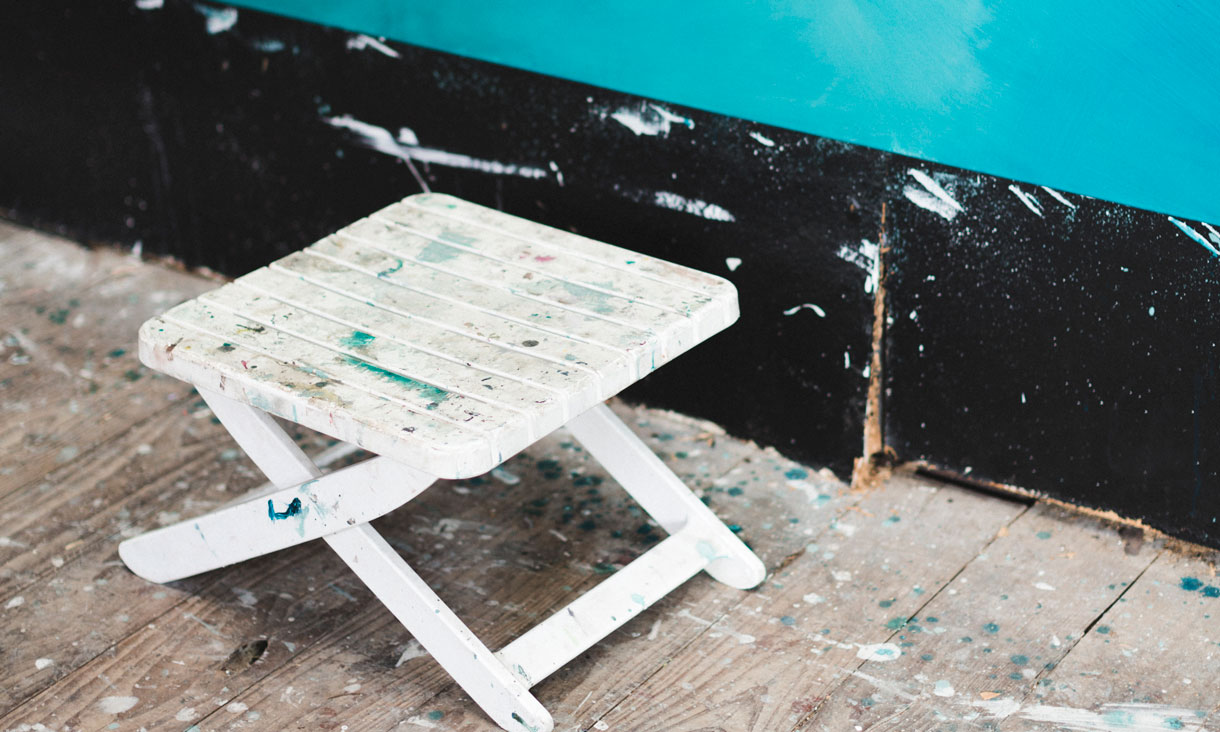 A stool covered in paint sits against the wall in Julian Clavijo's studio.
