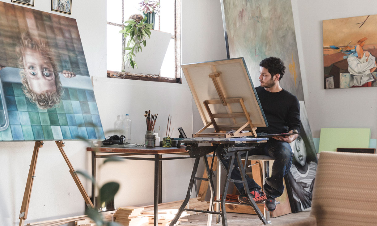 Julian paints seated behind his easel in his studio.
