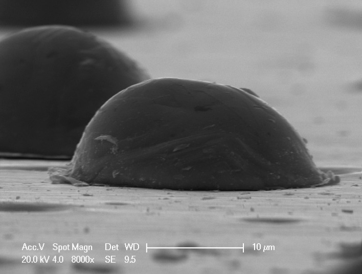Figure 2: SEM image of a cold sprayed titanium particle bonded to a steel surface.