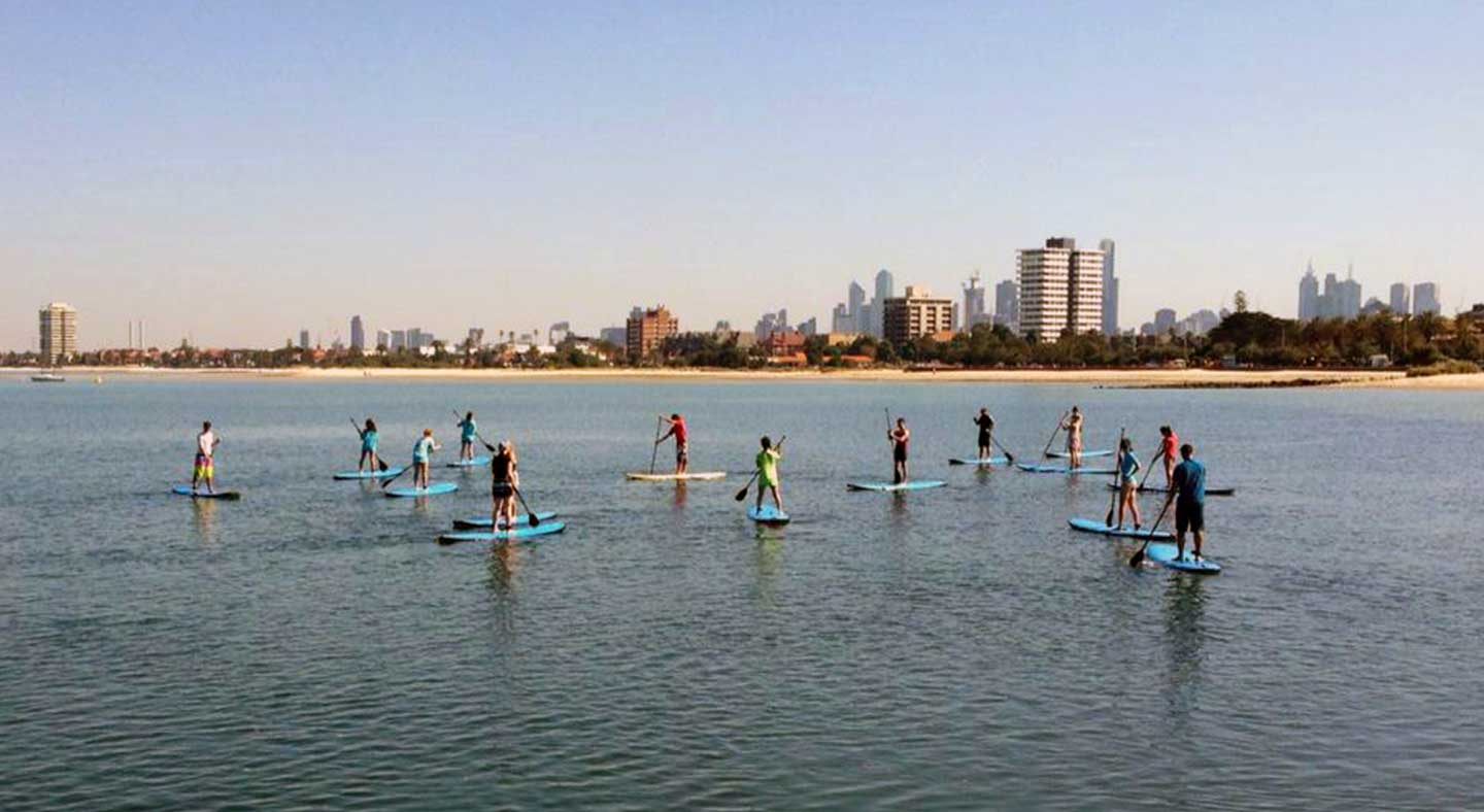 Students stand-up paddleboarding.