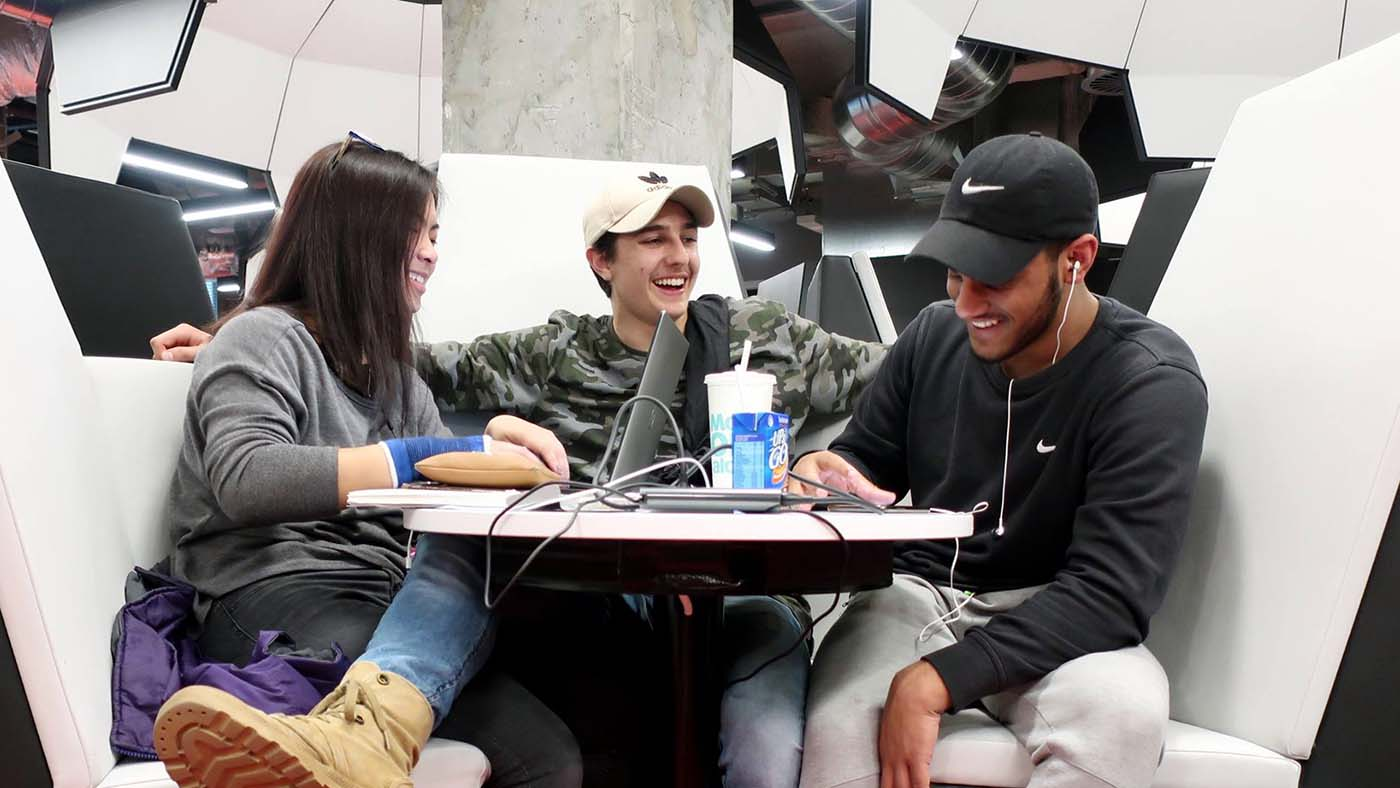 Three students sitting in a study space at the Swanston Library